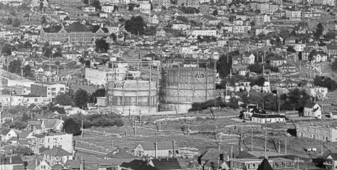"""""""COOK WITH GAS"""" signs can be found hanging on both of the Lower Queen Anne tanks in this view from upper Queen Anne aka """"The Hill."""" Part of the David and Louisa Denny orchard still flourished to the west (right) of the tanks, and to the right of the fruit trees the family home is still standing on the north side of Repubican between 8th Ave. and Dexter Street, although the Dennys have long-since move from there."""
