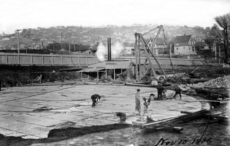 """The foundation for the first of two tanks, with the Queen Anne Hill horizon, as yet without Queen Anne High School (1909). This snapshot like most of the others in the """"Gas Album"""" is dated. Nearly a half year before the feature photo, this is November 10, 1906."""