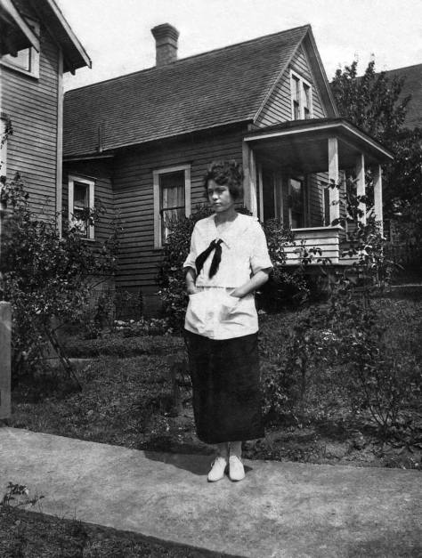 A grown Myrtle standing on the sidewalk to the birthing house, with the original family home behind her.