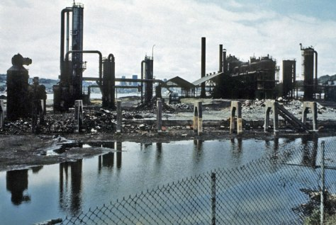 """THEN: The 1906-07 Gas Works at the north end of Lake Union went idle in 1956 when natural gas first reached Seattle by pipeline. In this photo, taken about fifteen years later, the Wallingford Peninsula is still home to the plant's abandoned and """"hanging gardens of metal."""" (Courtesy: Rich Haag)"""