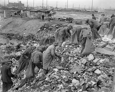 THEN: Unemployed men search for anything useful in land being reclaimed with city garbage used for fill on the tideflats. The date is March 6, 1937. The scene looks northwest from what was once near 7th Ave. S. and Forest Street, but is now inside the operations facilities for the Light Rail Division of Sound Transit. The Sears Department Store, now home of Starbucks Coffee Co., appears in the upper-left corner. Courtesy: The Post-Intelligencer Collection at the Museum of History and Industry.