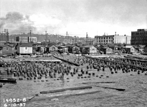 Hooverville from its dock on June 10, 1937. Note the Goodrich building right-of-center. The pilings are most likely remnants from the site's use for building ships during the First World War. (Courtesy, Seattle Municipal Archive)
