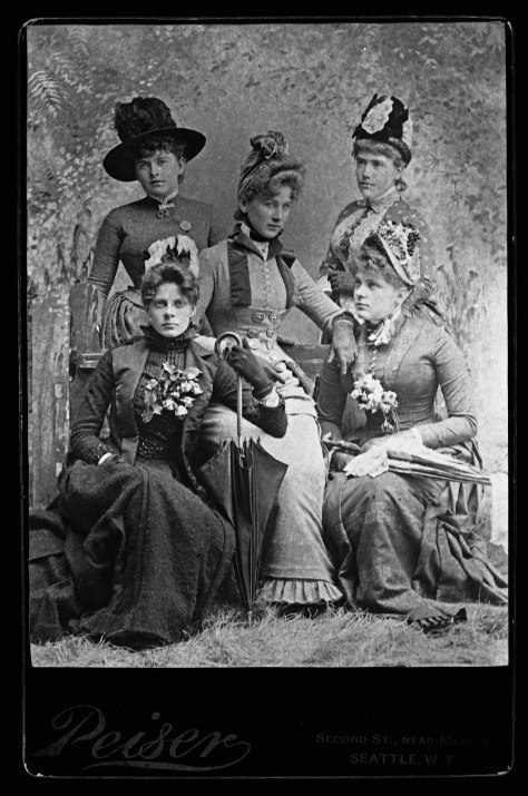 Peiser has persuaded five Seattle women to pose for him in this group portrait from the 1880s. At least, this is how we read it.