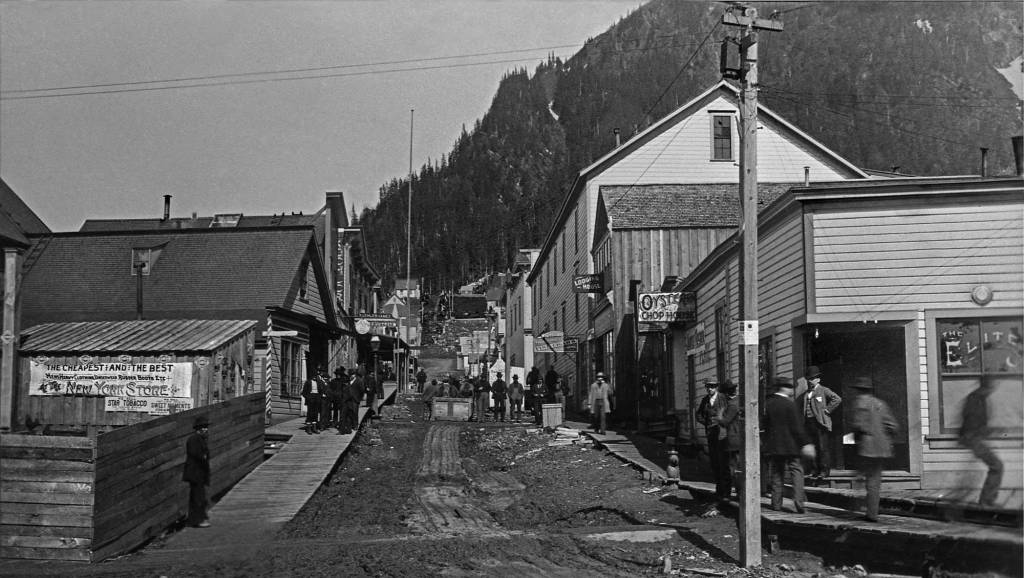 THEN: Photographer Frank LaRoche arrived in Seattle a few weeks after its Great Fire of 1889. Through the 1890s he made scores of round-trips to the Klondike, including this visit to the Juneau intersection of Seward Avenue and Front Street. (Museum of History and Industry)