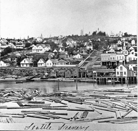 Looking east from the elbowed end of Yesler's Wharf to the waterfront at Columbia Street in 1878. The brewery is behind the first Colman Dock, far right. Columbia Street climbs First Hill from Front Street. In the foreground some of Henry Yesler's logs float in his mill pond.