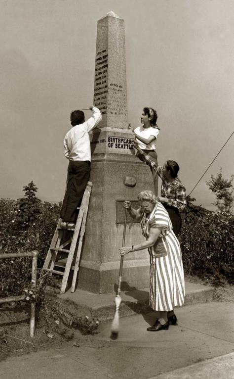Tidying the founder's pylon near Alki Point for Seattle's centennial in 1951.