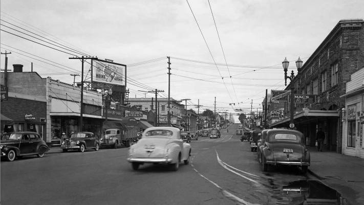 THEN: Looking into West Seattle's Junction and north on California Ave. SW to its intersection with SW Alaska Street in 1941. The Hamm Building, is seen above the light-colored car, and the Campbell Building is at right, behind the G.O. Guy Drugs sign.