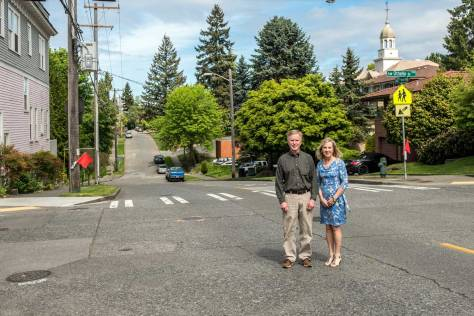 "NOW: Descendants Stuart and Michele Kenney pose at the same intersection, sans trestle. The former Ashton Grocery building, shown in the ""then"" view, remains, at left."