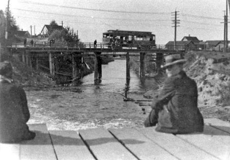 Enjoying the noontime sun while resting or fishing perhaps with a hidden pole on the bridge that cross the Lake's Fremont outlet. Beyond is the trolley bridge. The scene looks west towards Ross and Ballard.
