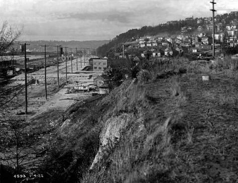 THEN: James P. Lee, Seattle's busy public works photographer of the early 20th century, recorded this 1922 look north from near the west end of Denny Way on the bluff above the then-forming Elliott Way. (Courtesy Museum of History and Industry)