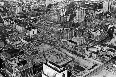 With the Federal Courthouse as 5th and Madison at the bottom, this aerial looks north-northeast at a stretch of freeway construction where I-5 curves from the city's grid as it approaches the western flank of Capitol Hill. A few of the surviving buildings noted in the paragraph below can be found here as well.