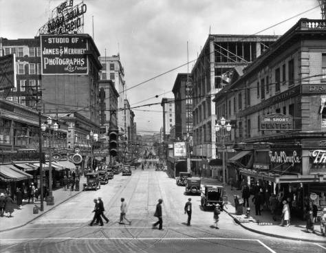 Pike looking east from the public market. You might pull the date by the motorcars or the construction work on the Bon Marche at the southeast corner of Pike and Second, here right of center.