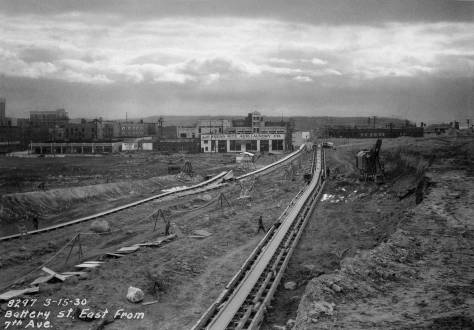 THEN: Looking west (not east) on Battery Street from Seventh Avenue, approaching the end of the last of Denny Hill's six regrade reductions. The dirt was carried to Elliott Bay on conveyor belts like the two shown here. (courtesy Seattle Municipal Archives)