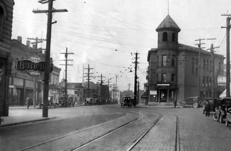 Looking northwest on Ballard Ave thru the slight jog at its intersection with 22nd Ave. N.W., with what was City Hall (before the 1907 annexation into Seattle proper) standing above the corner.