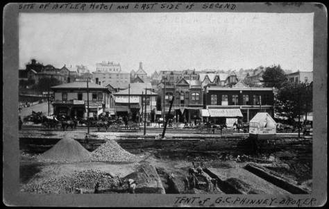 Guy Phinney's real estate tent stands on a scaffold near the northwest corner of Second Ave. and James Street, and the future front door to the Butler Hotel. The view of early construction following the Great Fire of June 6, 1889 looks east from Pioneer Square, near the center of the block between James and Cherry Streets.